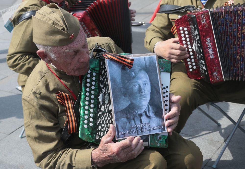 一名男子举着参加过伟大卫国战争的亲人的肖像