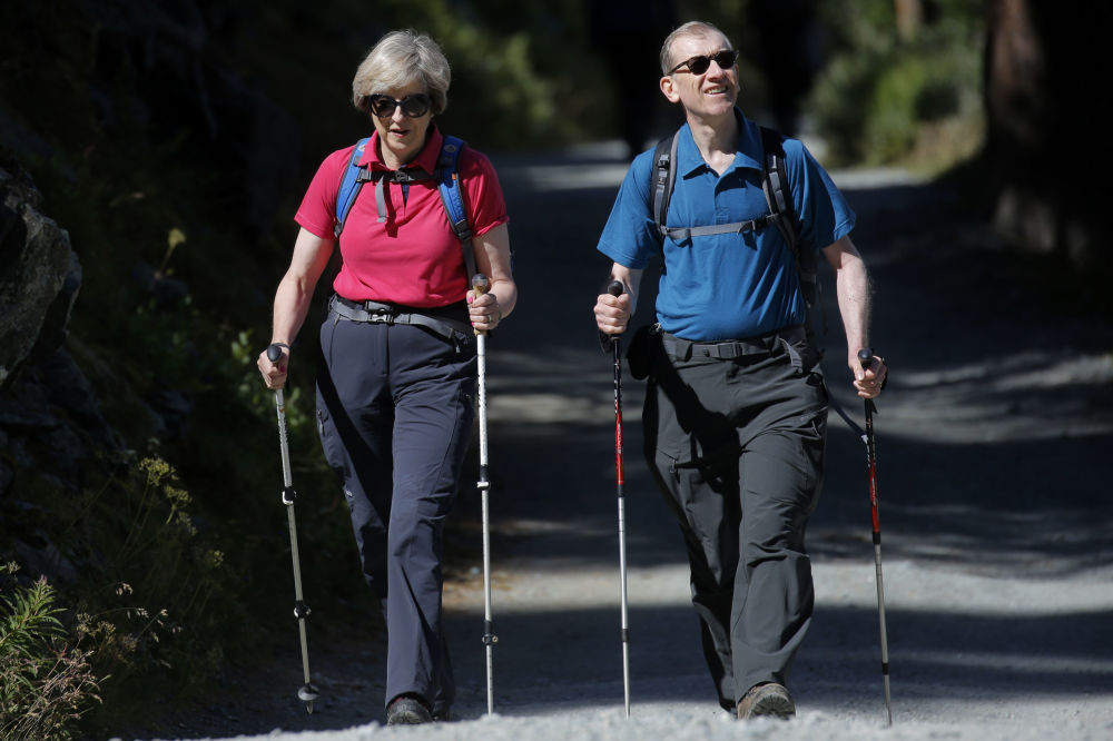 英国首相特蕾莎·梅与她的丈夫菲利普在瑞士林中散步。