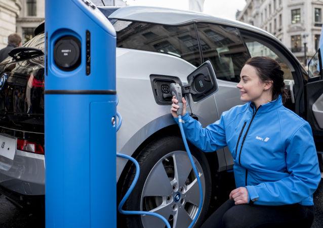 Девушка заряжает автомобиль на электростанции в Лондоне