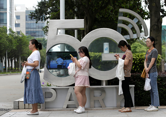 Employees wait for a shuttle bus at a 5G testing park at Huawei's headquarters in Shenzhen