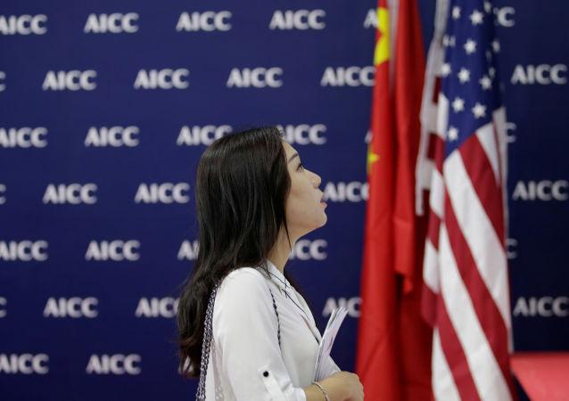 Женщина напротив флага США на Международной китайской выставке новейших технологий торговли услугами в Пекине
