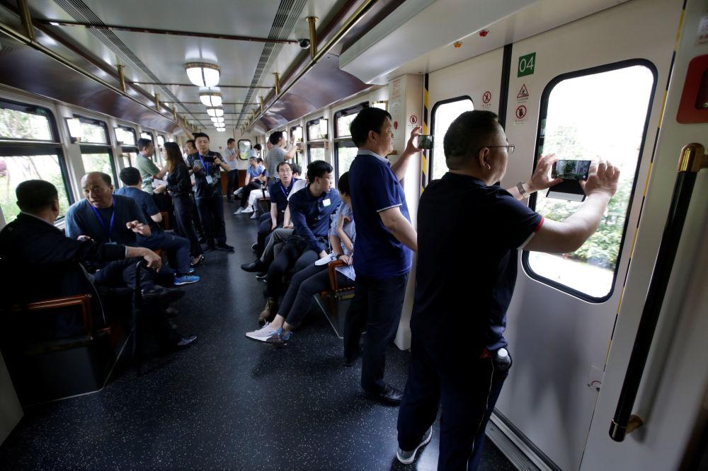 """华为公司办公室的访客在电气火车上拍摄。中国东莞。从""""牛角""""园区有电车和火车通往包括深圳总部在内的公司其他园区和中心"""