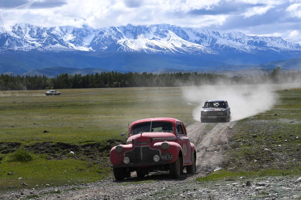 """参加""""2019北京—巴黎老爷车拉力赛""""的参赛者驾驶1941年雪佛兰超级豪华敞篷车和1972 年的VAZ-2103轿车行驶在俄罗斯阿尔泰共和国"""