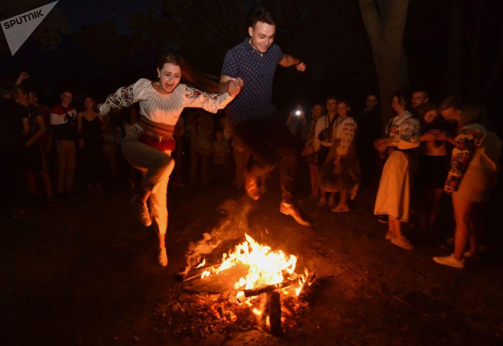 乌克兰小伙和姑娘在伊凡·库帕拉节上跳过篝火