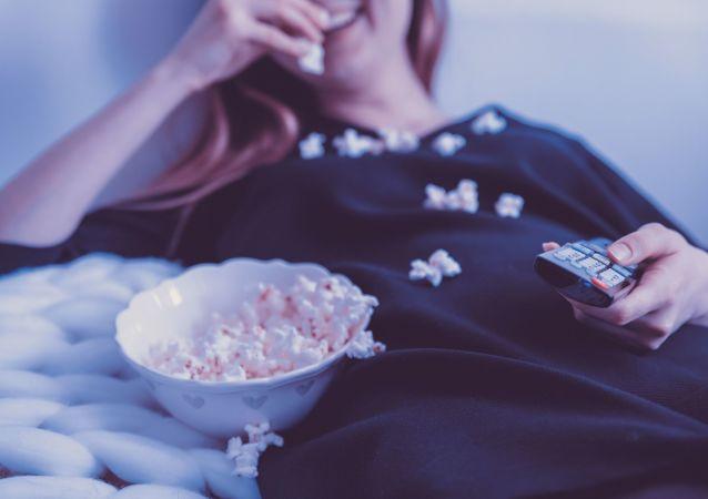 Девушка во время просмотра телевизора, лежа на диване