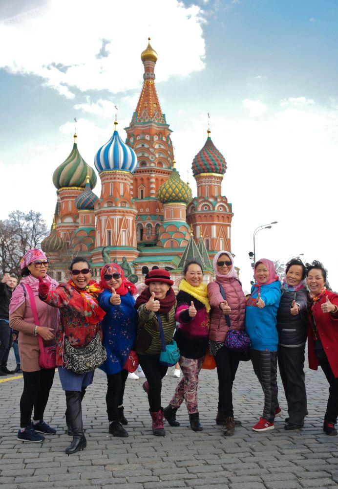 游客在莫斯科红场上的瓦西里·布拉任内教堂前拍照