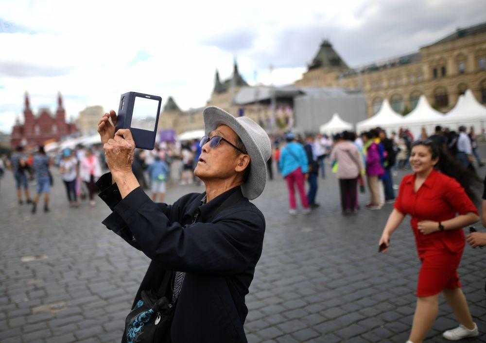 中国游客在红场上的莫斯科克里姆林宫前拍照