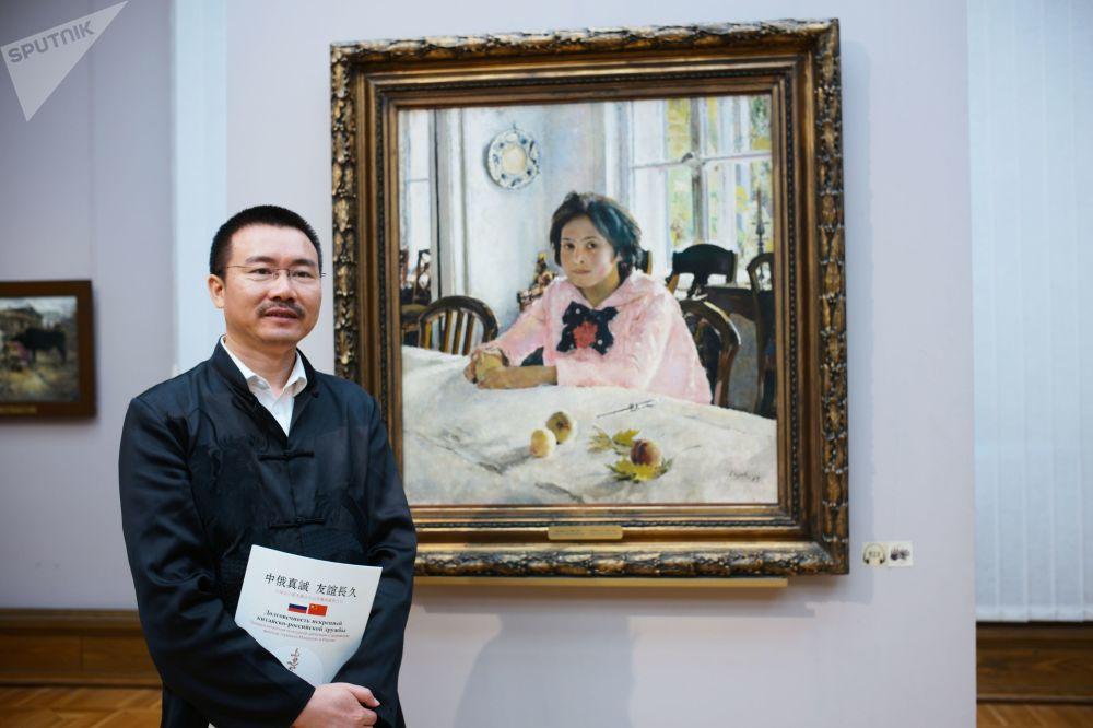一名中国游客在特列季雅可夫画廊画家谢洛夫的作品《少女和桃子》旁