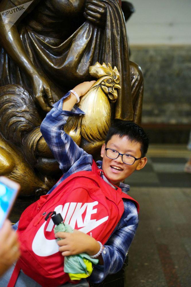 一名小男孩在莫斯科地铁的雕塑旁拍照