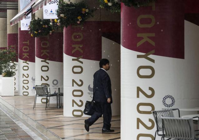 Мужчина на фоне баннеров с символикой Олимпиады-2020 в Токио