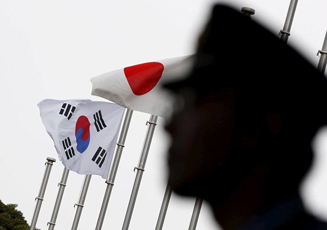 Военный на фоне японского и южнокорейского флагов