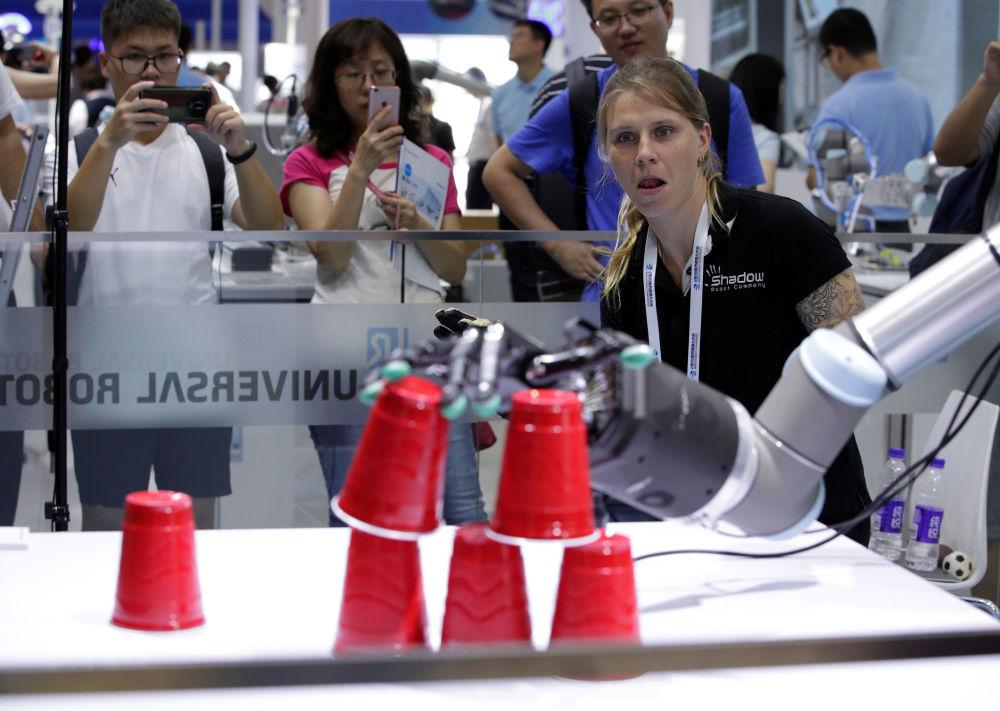 2019世界机器人大会上工程师借助遥控系统放置塑料杯。