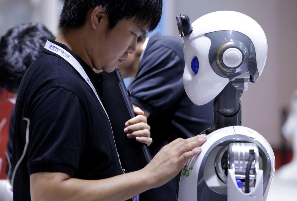 2019世界机器人大会表演前工程师给机器人CloudMinds安装5G标签。