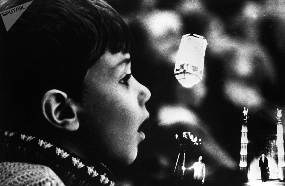 一名观看彩色林荫路马戏团舞台上马戏团演员和魔术师伊戈尔∙基奥表演的小观众