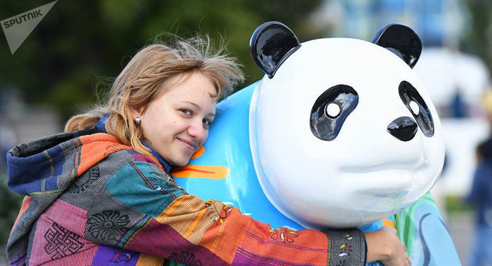 Девушка на выставке скульптур китайских панд на фестивале китайской культуры Китай: великое наследие и новая эпоха
