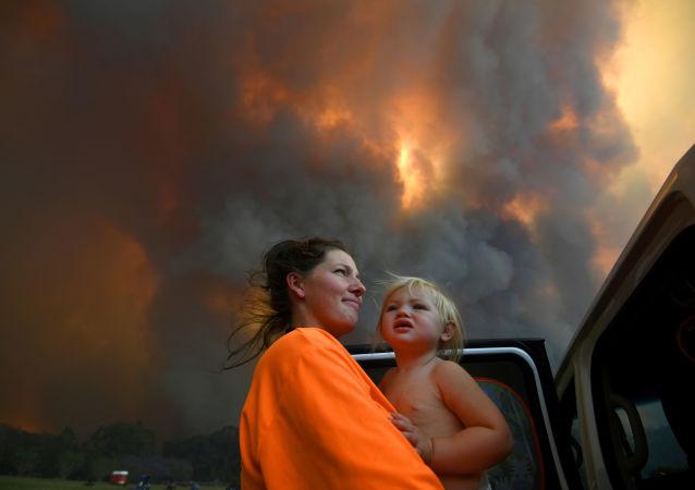澳大利亚自然火灾的烟雾中抱着孩子的女子。
