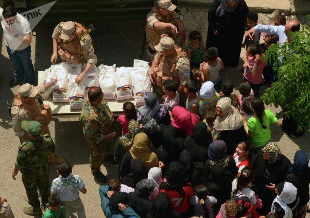 俄军将人道主义援助送至被武装分子摧毁的叙利亚村庄居民手中