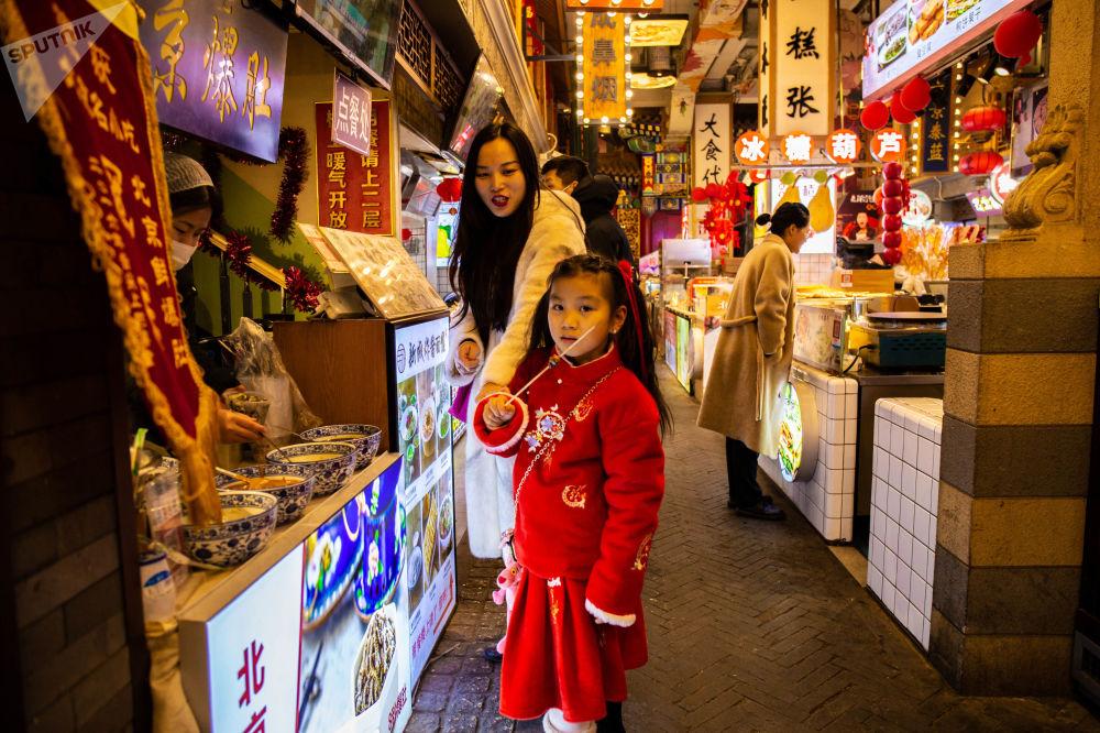 大人带着孩子在假期前来前门大街品尝传统糕点
