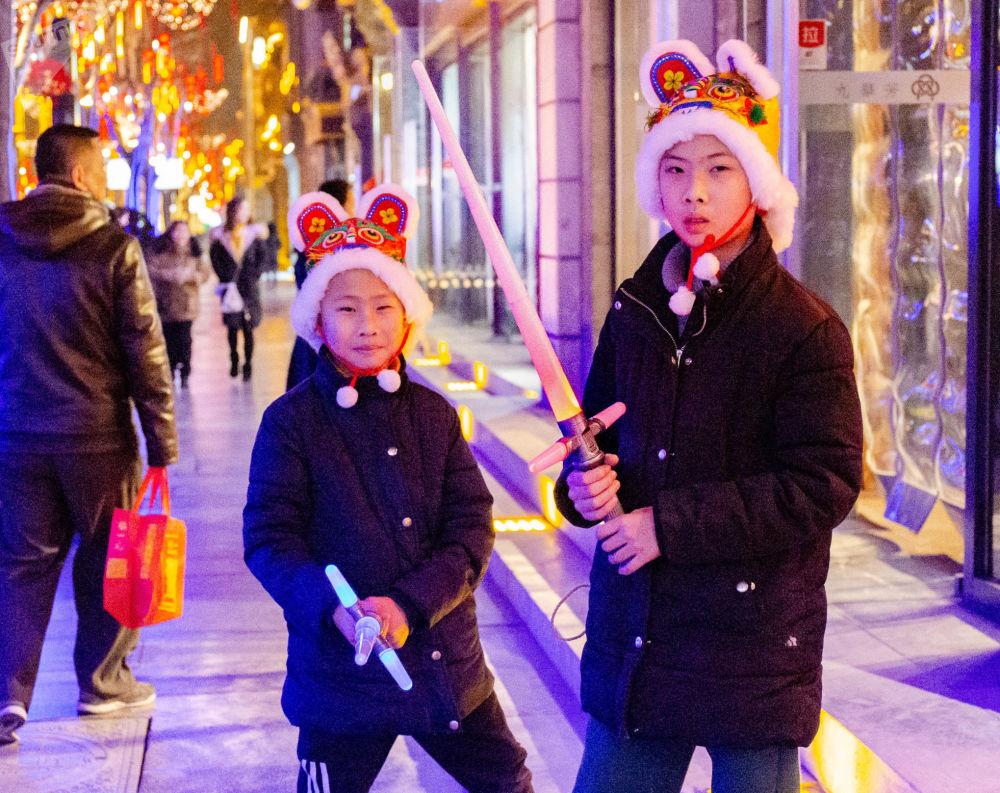 戴着新年帽子的兄弟俩在玩耍宝剑