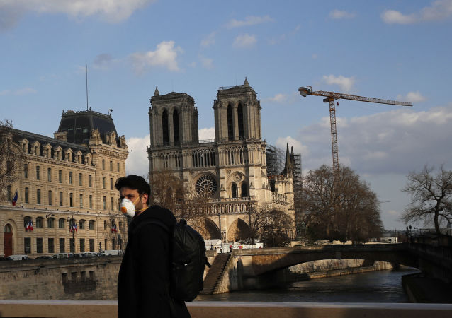 A masked man walks next to Notre Dame Cathedral, in Paris, Wednesday, March 18, 2020.