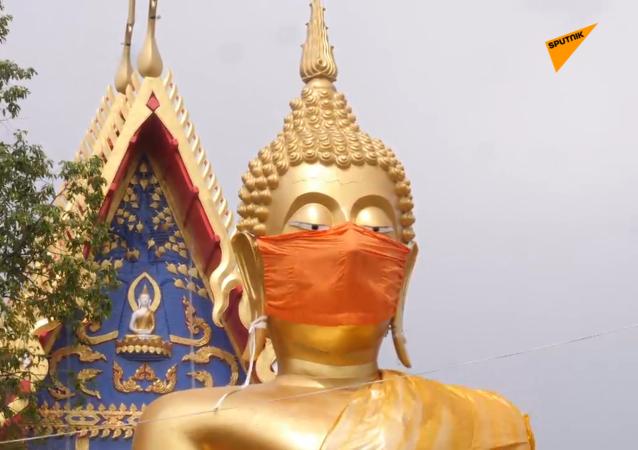 泰国佛像被戴口罩 提醒民众疫情期间遵守安全措施
